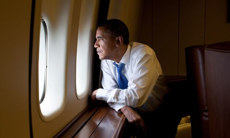 President Obama looks out the window aboard Air Force One.