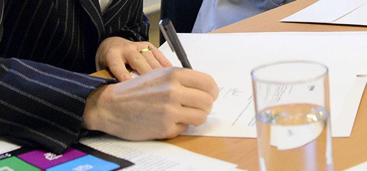 Primer plano de una mano de mujer firmando un documento