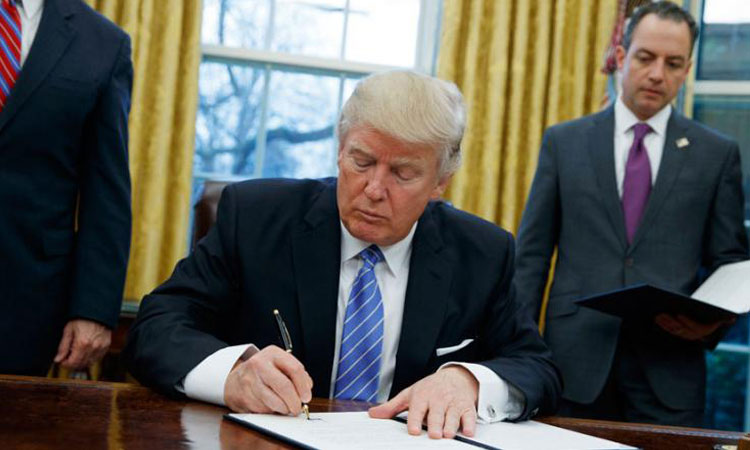 President Donald Trump signs an executive order to withdraw the U.S. from the 12-nation Trans-Pacific Partnership trade pact.